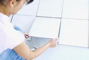 Young woman laying floor tiles